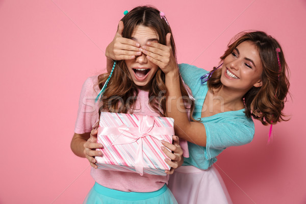 Young attractive girl in colorful tshirt surprises her friend wh Stock photo © deandrobot