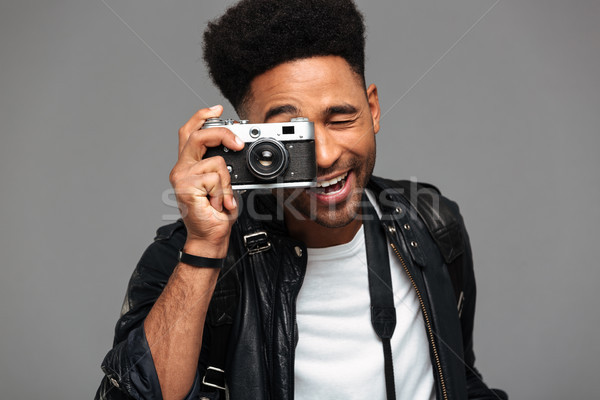 Portrait of a happy afro american guy in leather jacket Stock photo © deandrobot