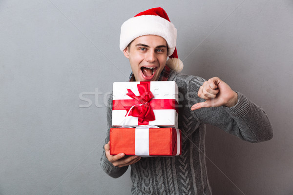 Funny man in sweater and christmas hat holding gifts Stock photo © deandrobot
