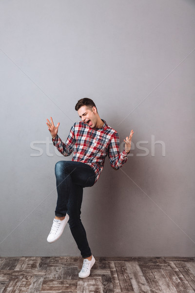 Full-length image of Cheerful screaming man in shirt and jeans Stock photo © deandrobot