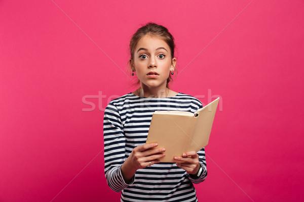 Teenage shocked girl holding book. Stock photo © deandrobot