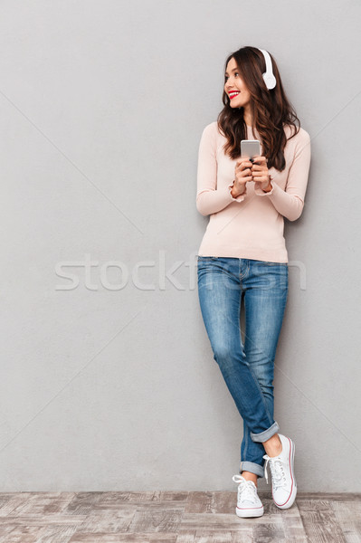 Full-length photo of beautiful female wearing sneakers and jeans Stock photo © deandrobot