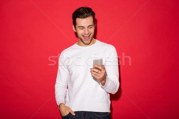 Obraz wesoły człowiek sweter smartphone czerwony Zdjęcia stock © deandrobot