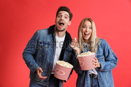 Laughing punk couple eating popcorn and looking at the camera Stock photo © deandrobot