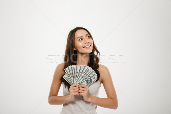 Portrait of successful young woman with long hair holding lots o Stock photo © deandrobot