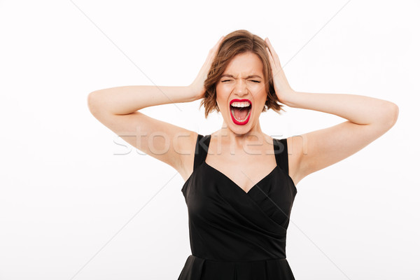 Portrait of a frustrated girl dressed in black dress screaming Stock photo © deandrobot