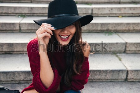 Smiling brunette woman in hat and sweater sitting on stairs Stock photo © deandrobot