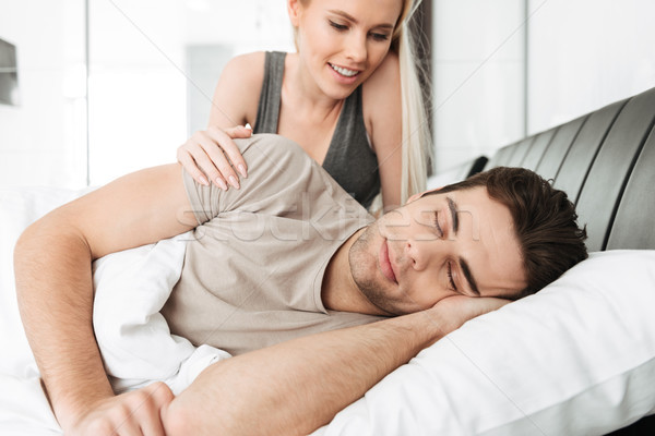 Smiling pretty lady waking her sleeping husband in the bed Stock photo © deandrobot