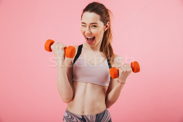Happy screaming sportswoman doing exercise with dumbbells Stock photo © deandrobot