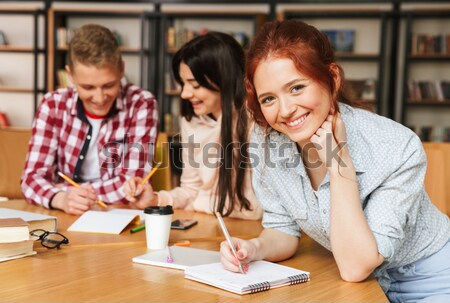 Grupy uśmiechnięty nastolatków praca domowa posiedzenia biblioteki Zdjęcia stock © deandrobot