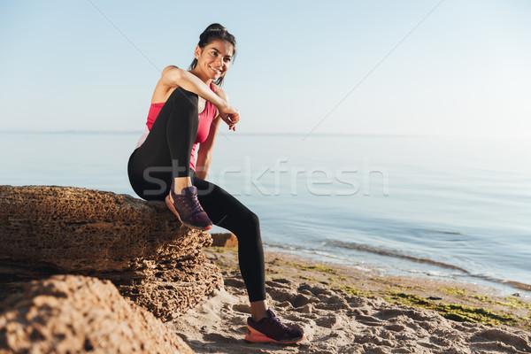 笑みを浮かべて 小さな スポーツウーマン 座って 岩 ビーチ ストックフォト © deandrobot