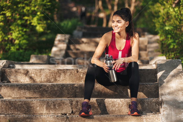 Smiling young sportswoman sitting on stairs with water bottle Stock photo © deandrobot