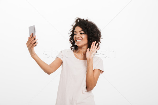Joyful woman 20s with curly hair wearing basic t-shirt holding m Stock photo © deandrobot