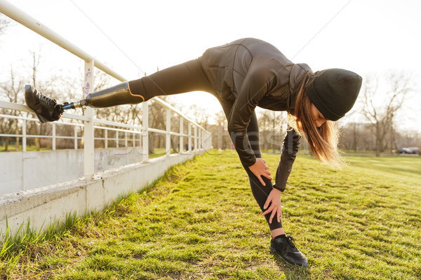 Photo of disabled running woman in sportswear, doing slopes and  Stock photo © deandrobot