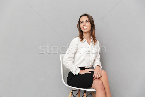 Cheerful young business woman looking aside. Stock photo © deandrobot