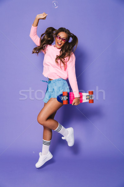 Full length portrait of attractive skater girl with two ponytail Stock photo © deandrobot