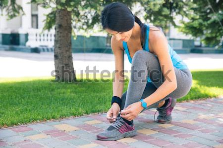 Woman tying her shoelace outdoors Stock photo © deandrobot