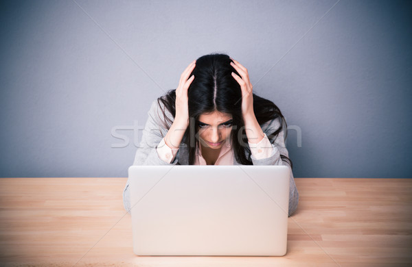 Tired businesswoman sitting at the table  Stock photo © deandrobot
