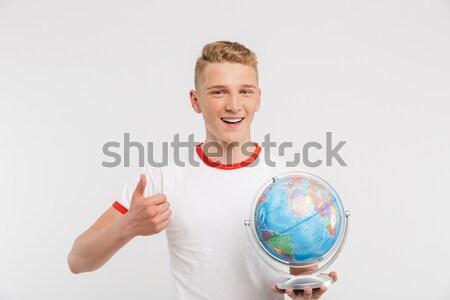 Stock fotó: Boldog · férfi · mutat · ujj · földgömb · fiatalember