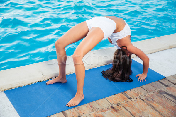 Woman doing yoga bridge pose outdoors  Stock photo © deandrobot