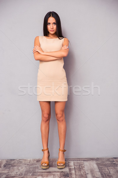 Stock photo: Full length portrait of a serious woman with arms folded