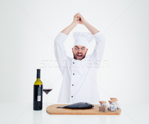 Portrait of angry male chef cook cutting fish  Stock photo © deandrobot