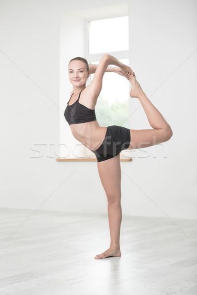 Smiling woman doing yoga exercises in gym Stock photo © deandrobot