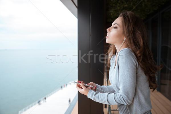 Mulher jovem em pé varanda ouvir música atraente belo Foto stock © deandrobot