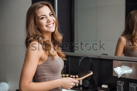 Stock photo: Beautiful young female holding comb and smiling