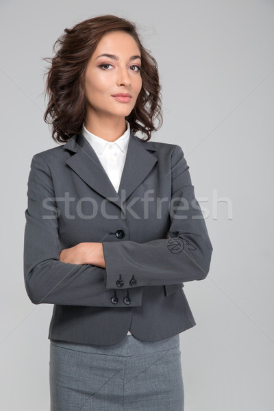 Smug young business woman with arms crossed  Stock photo © deandrobot