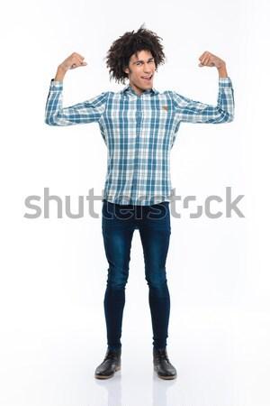 Derűs afro amerikai férfi mutat bicepsz Stock fotó © deandrobot