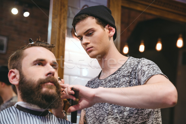 Young skillful barber making haircut to handsome bearded man Stock photo © deandrobot