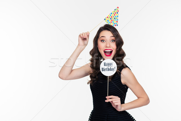 Stock photo: Smiling joyful pretty curly woman posing with birthday props isolated