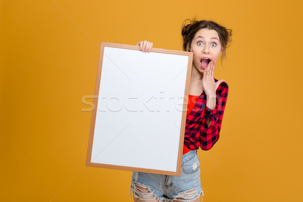 Amazed happy young woman holding blank board Stock photo © deandrobot