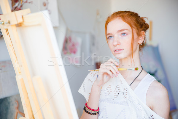 Thoughtful woman painter standing in front of easel with paintbrush Stock photo © deandrobot