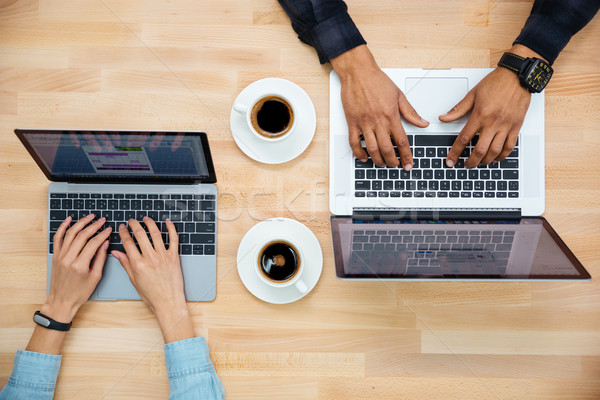 Top view of man and woman working with two laptops  Stock photo © deandrobot