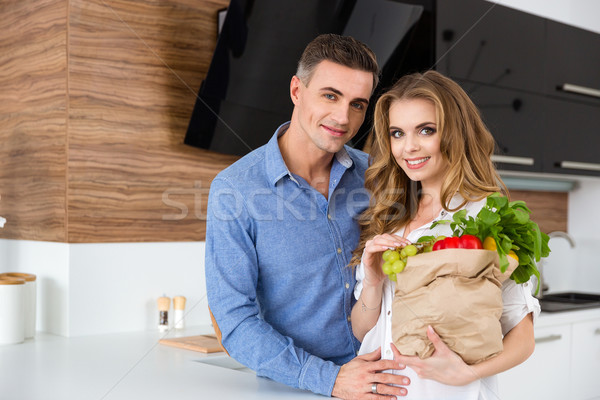 Beautiful couple holding paper packet of food  Stock photo © deandrobot