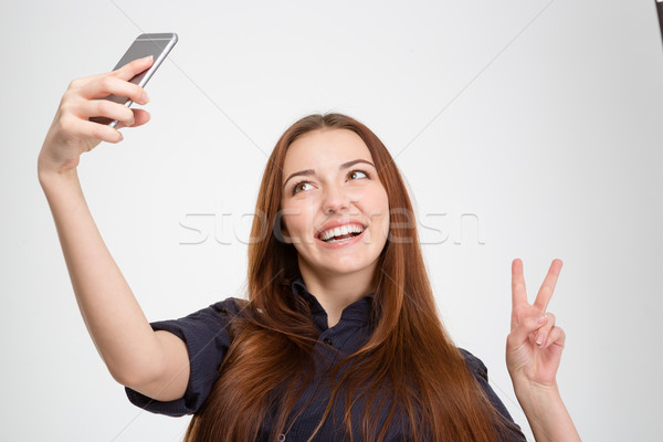 Glimlachende vrouw mobiele telefoon tonen overwinning teken Stockfoto © deandrobot