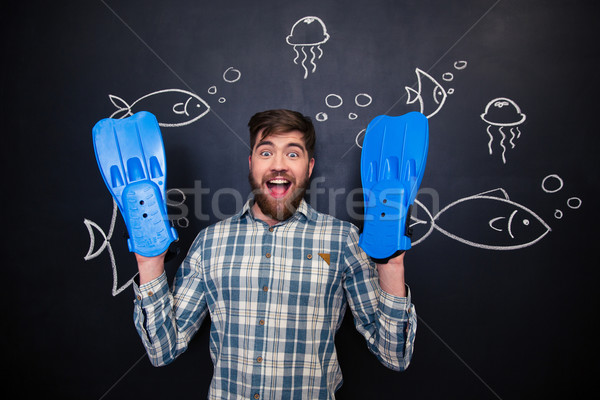 Excited man with flippers on hands standing over  blackboard background Stock photo © deandrobot