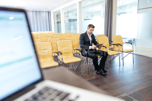 Pensive focused businessman using tablet in empty conference hall Stock photo © deandrobot