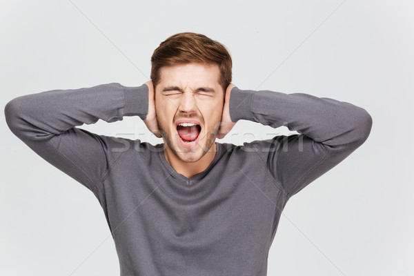 Depressed upset young man covered ears by hand and shouting Stock photo © deandrobot