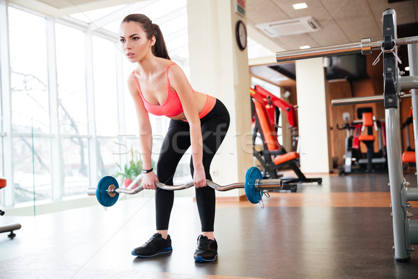Beautiful young sportswoman doing exercises with barbell in gym Stock photo © deandrobot