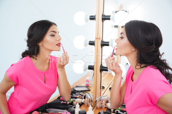 Beautiful woman standing near mirror and putting on red lipstick  Stock photo © deandrobot