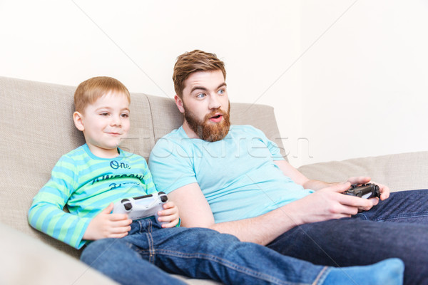 Amazed father playing computer games with his son on sofa  Stock photo © deandrobot