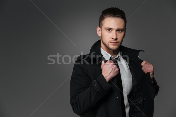 Closeup of handsome young businessman in black coat Stock photo © deandrobot