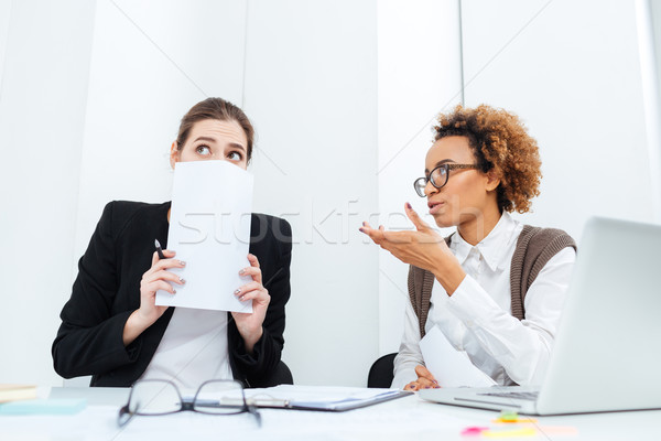 Strict african businesswoman director talking with her scared young employee  Stock photo © deandrobot