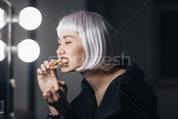 Funny woman in blonde wig eating pizza in dressing room Stock photo © deandrobot