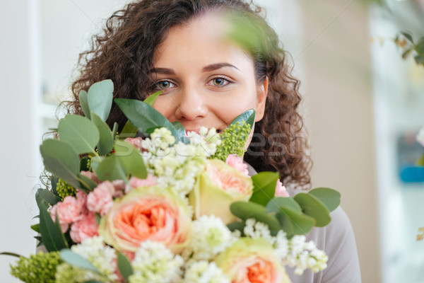 Happy woman holding bouquet of flowers and smiling Stock photo © deandrobot