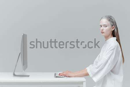 Woman sitting at the desk with computer, pc Stock photo © deandrobot