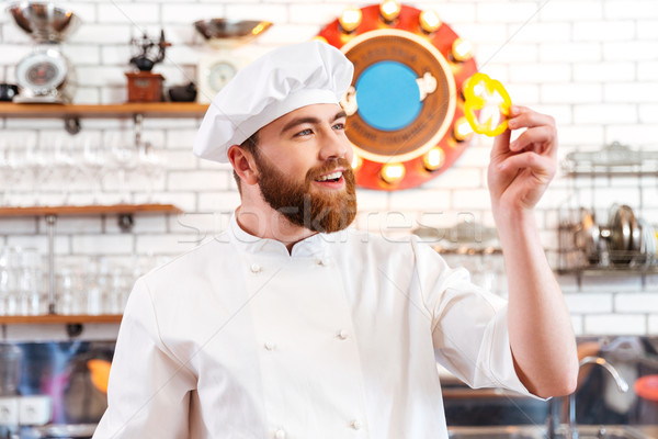 Smiling cook cheif holding slice of yellow bell pepper  Stock photo © deandrobot